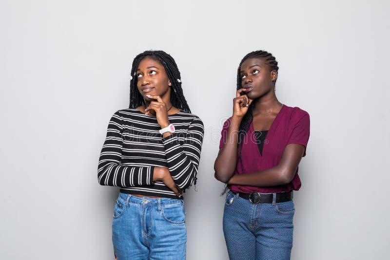 Stående av två le unga afrikanska kvinnor som tillsammans står uttråkat som isoleras över vit bakgrund arkivfoto