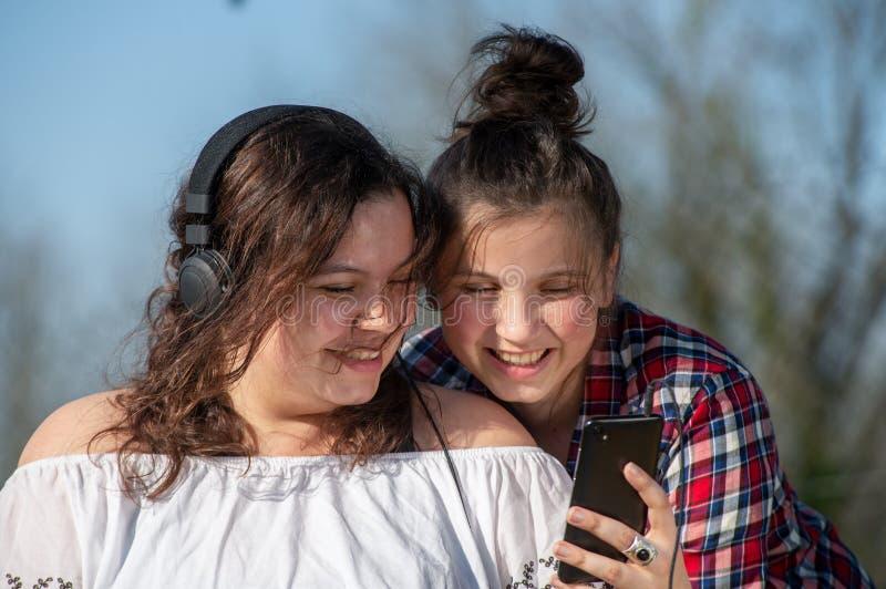 St?ende av tv? lyckliga systrar med smartphonen, utomhus royaltyfri fotografi
