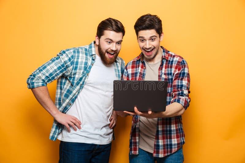 Stående av två lyckliga unga män som använder bärbar datordatoren royaltyfri fotografi