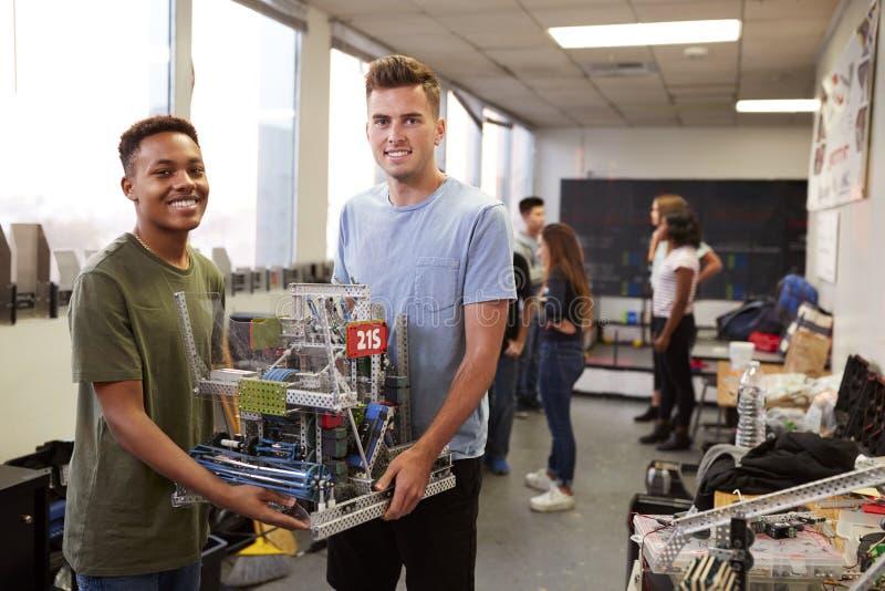 Stående av två manliga universitetsstudenter som bär maskinen i vetenskapsrobotteknik eller iscensätter grupp arkivfoto
