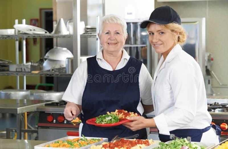 Stående av två matställedamer i skolakafeteria royaltyfri fotografi