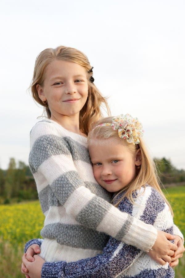 Stående av två omfamna gulliga liten flicka arkivbilder