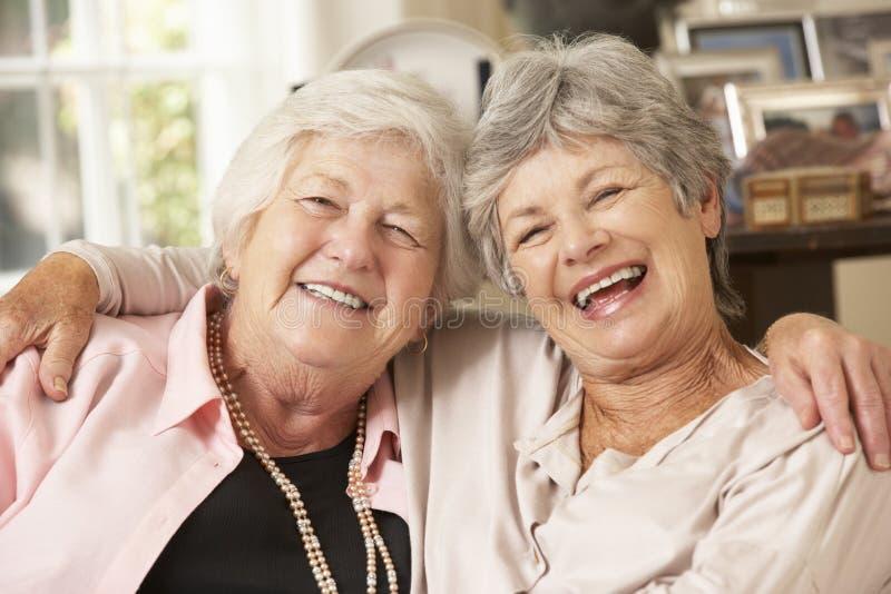 Stående av två pensionerade höga kvinnliga vänner som sitter på soffan royaltyfri bild