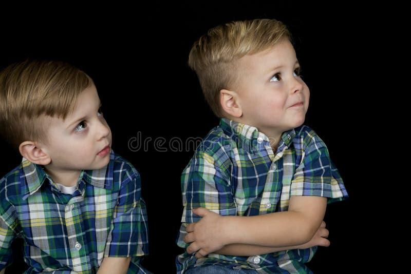 Stående av två pojkar som bär matcha skjortor som bort ser upp fotografering för bildbyråer