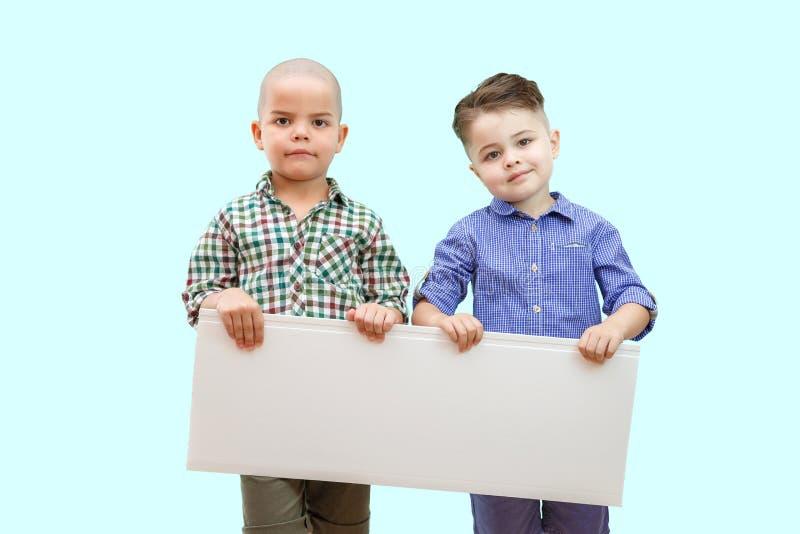 Stående av två pojkar som rymmer det vita tecknet på isolerad bakgrund royaltyfri foto