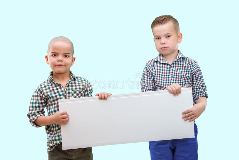 Stående av två pojkar som rymmer det vita tecknet på isolerad bakgrund royaltyfri fotografi