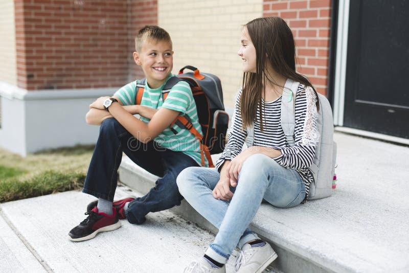 Stående av två skolavänner med ryggsäckar fotografering för bildbyråer
