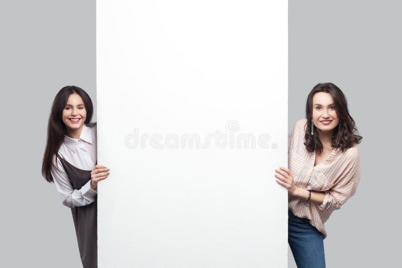 Stående av två tillfredsställda unga kvinnor för härlig brunett i tillfällig stil som står nära tom vit tom copyspace och ser arkivfoto