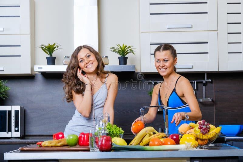 Stående av två tvilling- systrar som har gyckel i morgonen som förbereder frukosten royaltyfria bilder