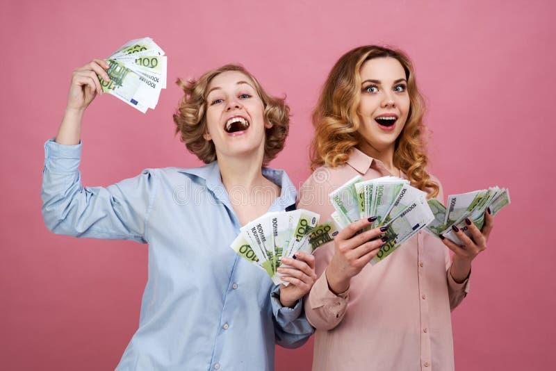 Stående av två unga europeiska flickor med kontant euro i hand och lyckligt glat uttryck De är förtjusta pengarna royaltyfri bild