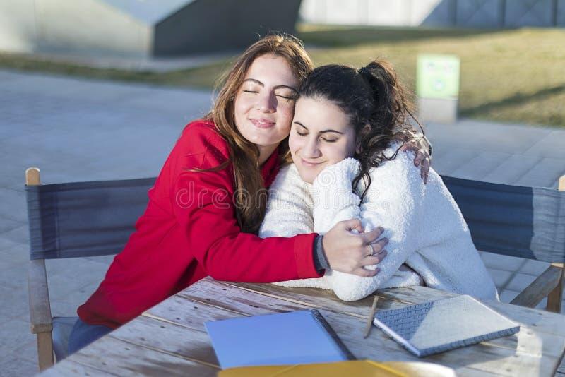 Stående av två unga kvinnor i ett utomhus- kafé, medan krama royaltyfri foto