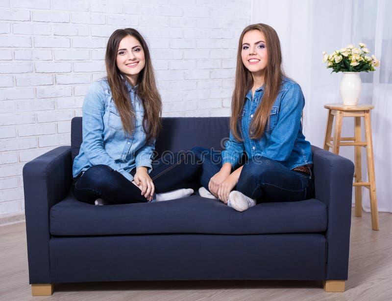 Stående av två unga kvinnor som sitter på soffan i vardagsrum fotografering för bildbyråer