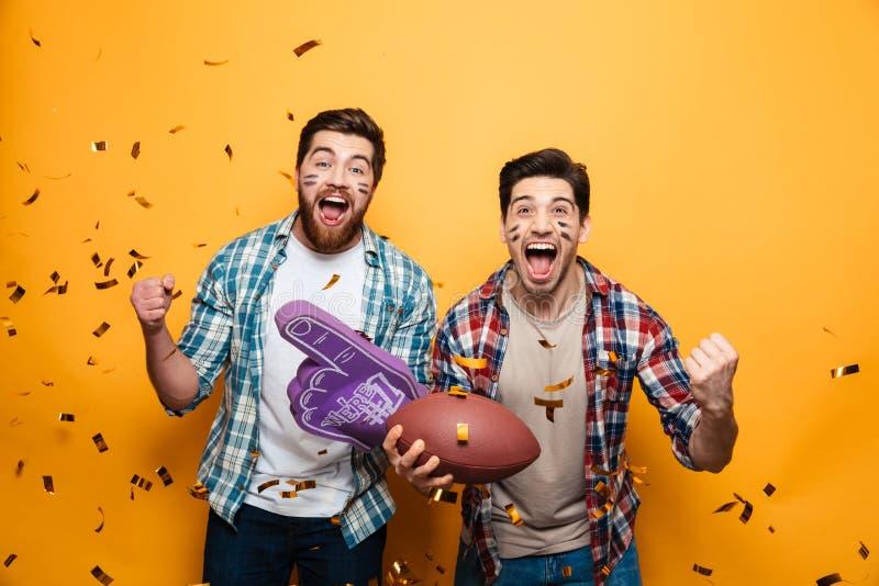 Stående av två upphetsade unga män som rymmer rugbybollen royaltyfri bild