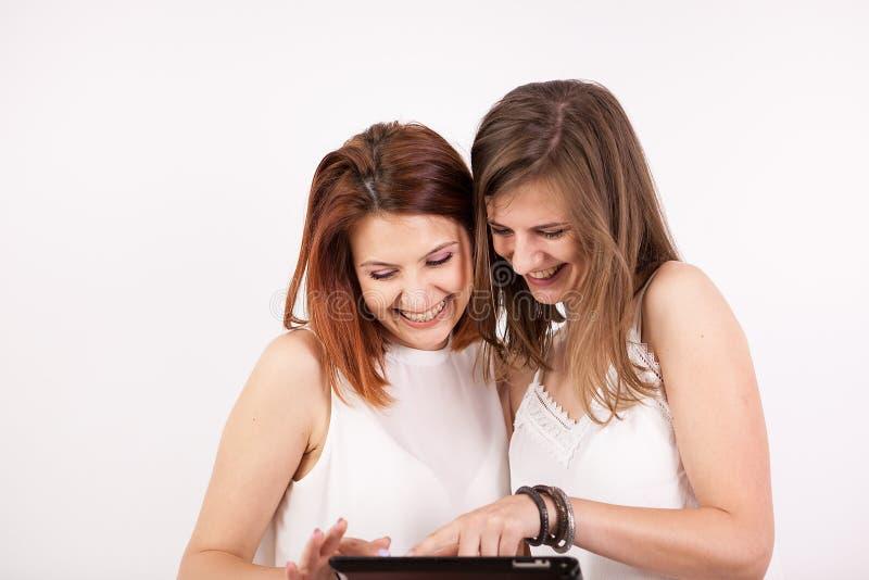 Stående av två ursnygga kvinnor som rymmer en minnestavlaPC fotografering för bildbyråer