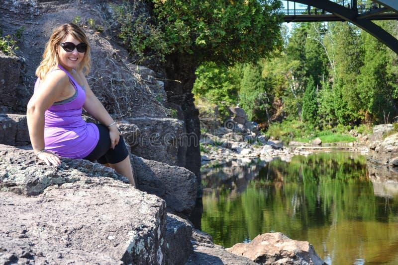 Stående av ung bärande solglasögon för en vuxen kvinna och lesammanträde på det fria för en klippa nära en lugna flod i Minnesota royaltyfria bilder