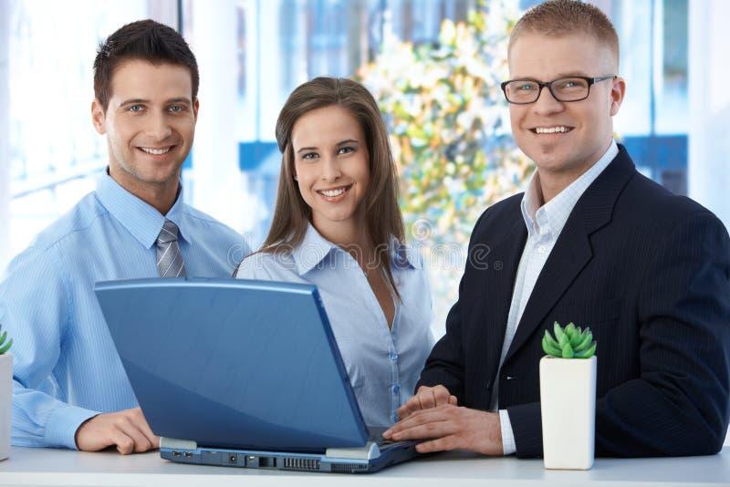 Stående av ung businessteam med bärbar dator royaltyfri foto