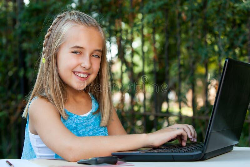 Gullig flicka som utomhus gör läxa på bärbar dator. fotografering för bildbyråer