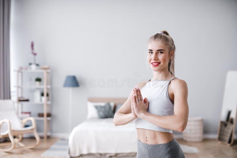 Stående av ung le övande yoga för yogikvinna som mediterar royaltyfri bild