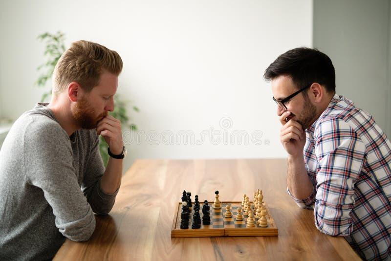 Stående av ung man som två spelar schack fotografering för bildbyråer