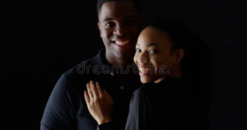 Stående av unga afrikanska par som rymmer sig som ler royaltyfria bilder