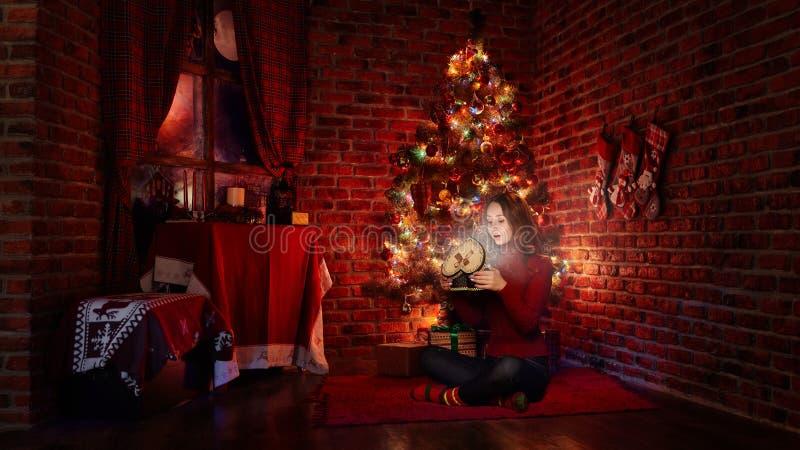 Stående av unga flickan med gåvan nära julgranen arkivbild