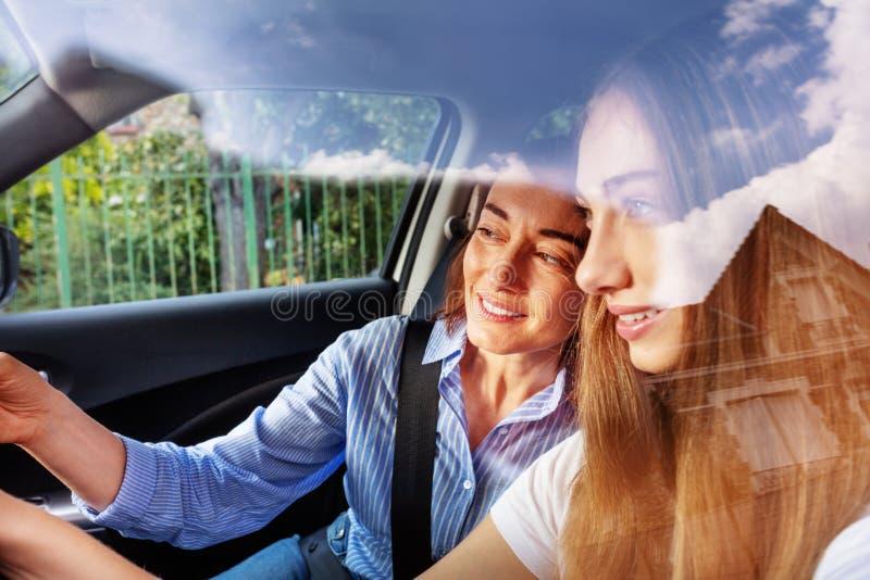 Stående av unga flickan som kör bilen med hennes moder arkivfoton