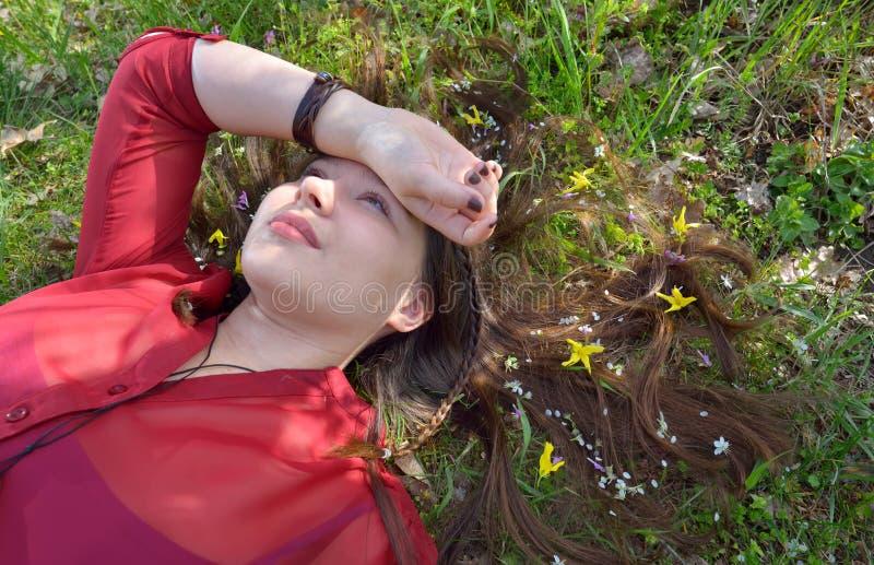 Stående av unga flickan som lägger på gräs fotografering för bildbyråer