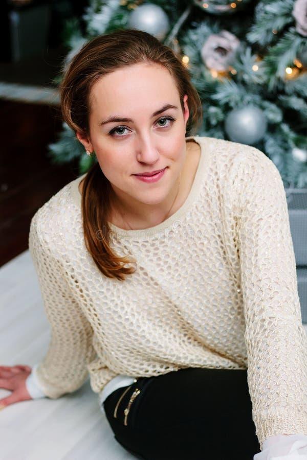 Stående av unga flickan som sitter nära julträdet arkivfoton
