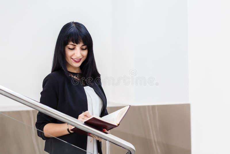 Stående av unga härliga lyckliga den iklädda brunettkvinnan en svart affärsdräkt som arbetar med en anteckningsbok som i regering arkivfoton