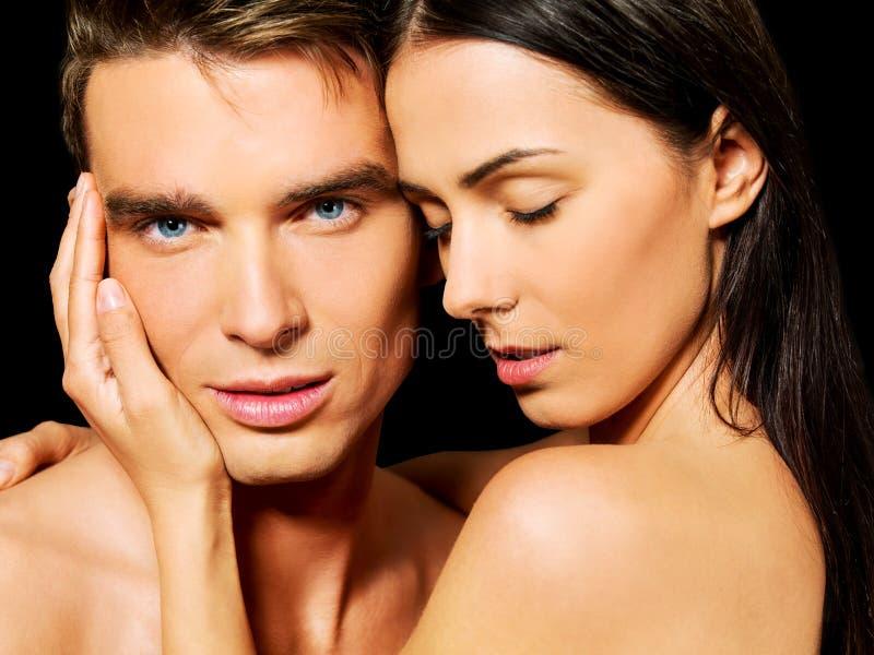 Stående av unga heterosexuella par som älskar sig med passion arkivfoton