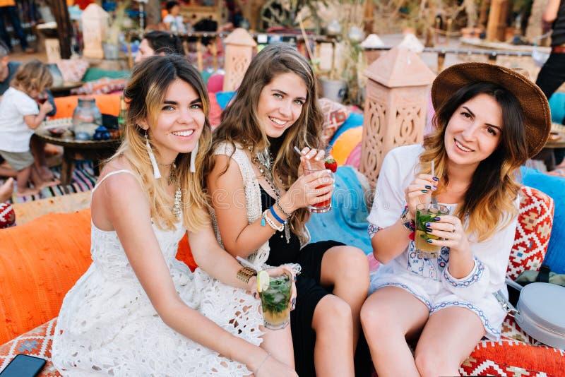 Stående av unga kvinnor som tillsammans spenderar tid efter arbete och sitter i frilufts- restaurang med smakliga coctailar tre royaltyfri foto