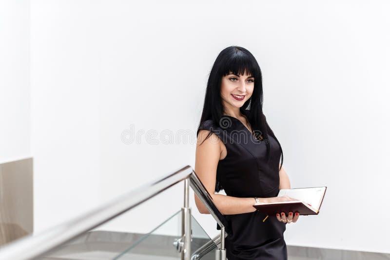 Stående av unga nätta lyckliga den iklädda brunettkvinnan en svart affärsdräkt som arbetar med en anteckningsbok som står i ett k royaltyfria bilder