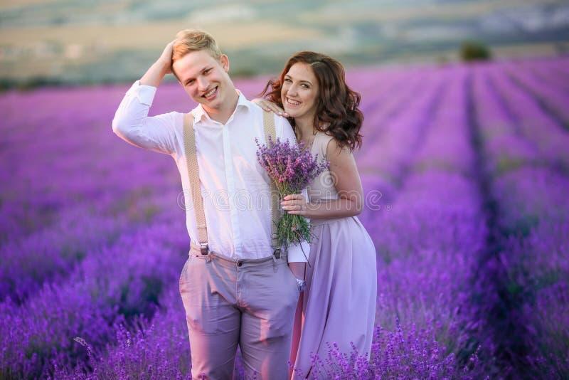 Stående av unga sinnliga älska par i ett lavendelfält på solnedgången france provence royaltyfria bilder