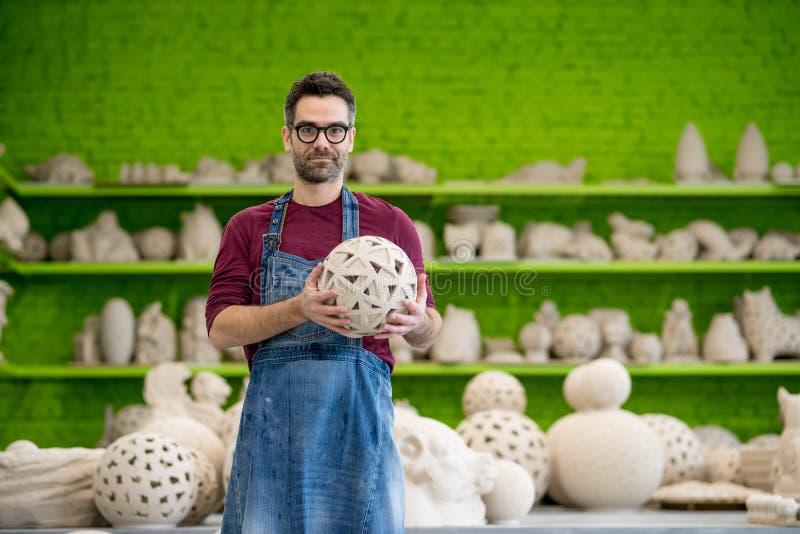 Stående av unga SmilingCeramist i den ljusa moderna keramiska seminariuminnehavskulpturen små och medelstora företagbegrepp royaltyfria foton