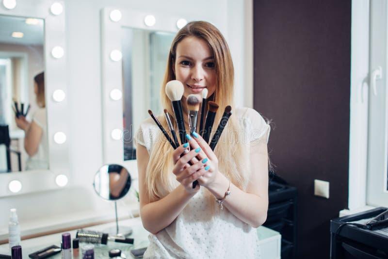 Stående av unga sminkkonstnärer som visar henne borstar som ser kameran i skönhetstudio arkivbilder