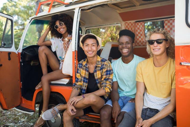 Stående av unga vänner som sitter i campareskåpbil arkivfoton