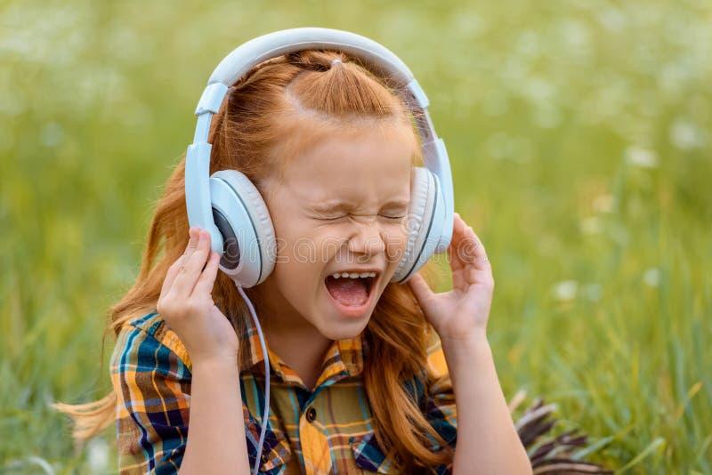 stående av ungen som skriker medan lyssnande musik i hörlurar med grönt gräs royaltyfria bilder