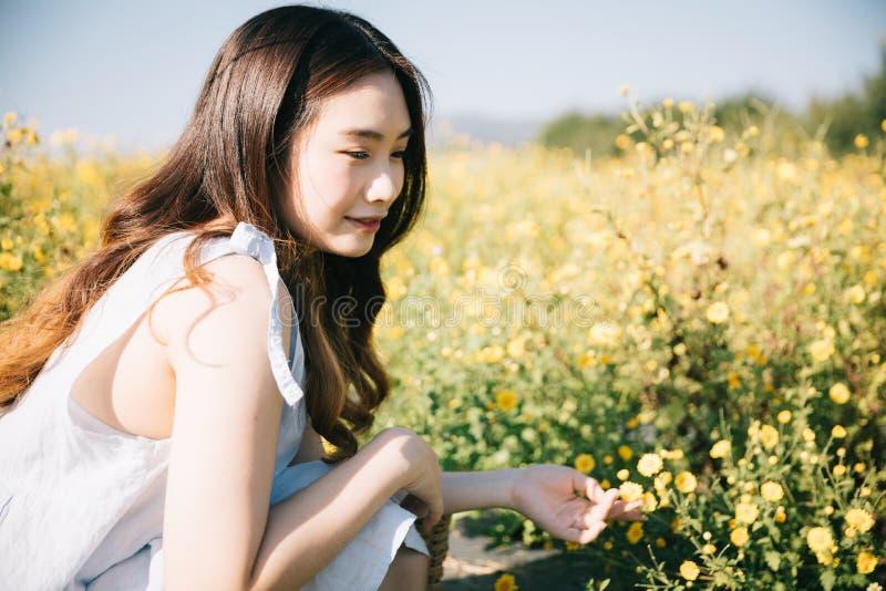 Stående av ungt asiatiskt det kvinnaflickasammanträde och leendet i blommaträdgård arkivbilder
