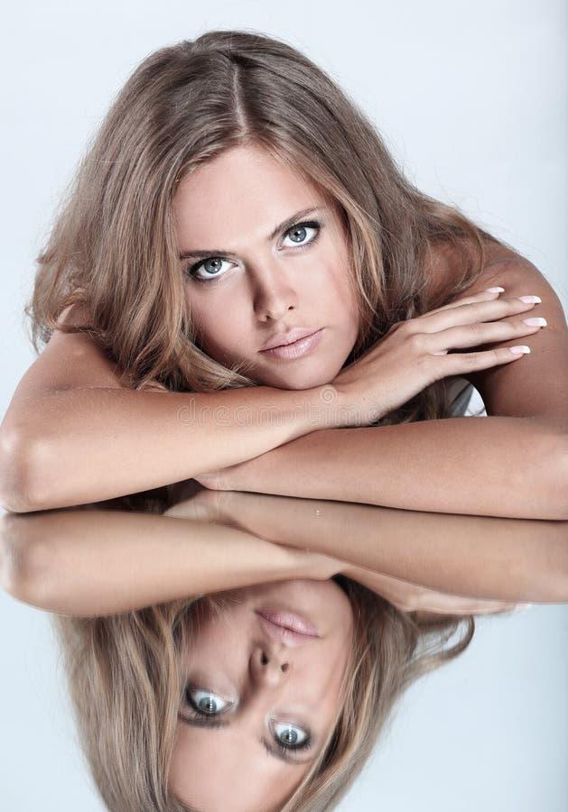 Stående av ungt härligt brunettkvinnasammanträde på spegelfliken arkivfoton