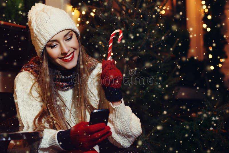 Stående av ungt härligt kvinnasammanträde i gatakafét och att se i hennes smartphone Dam som bär den stilfulla klassikern royaltyfria bilder