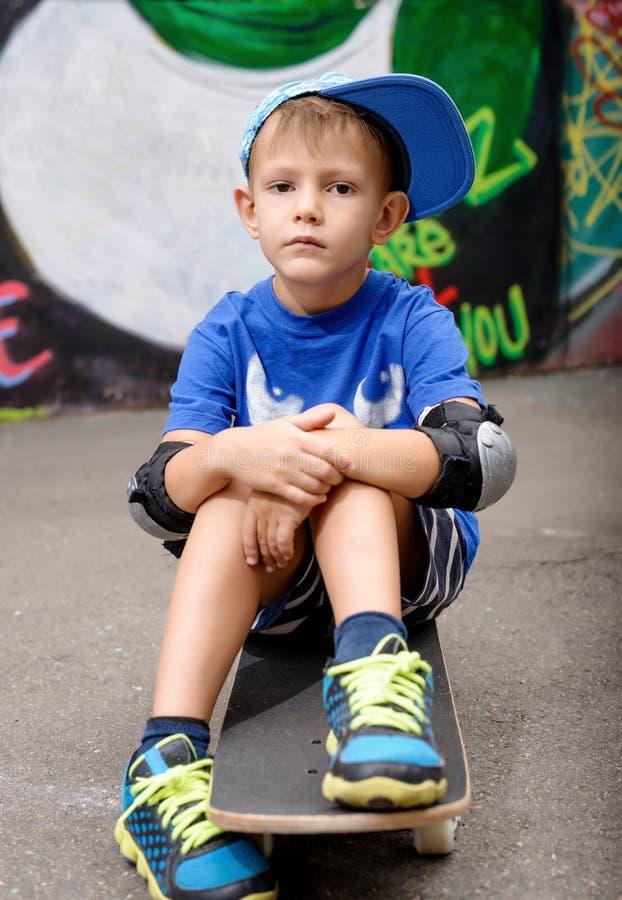 Stående av ungt pojkesammanträde på skateboarden royaltyfria foton