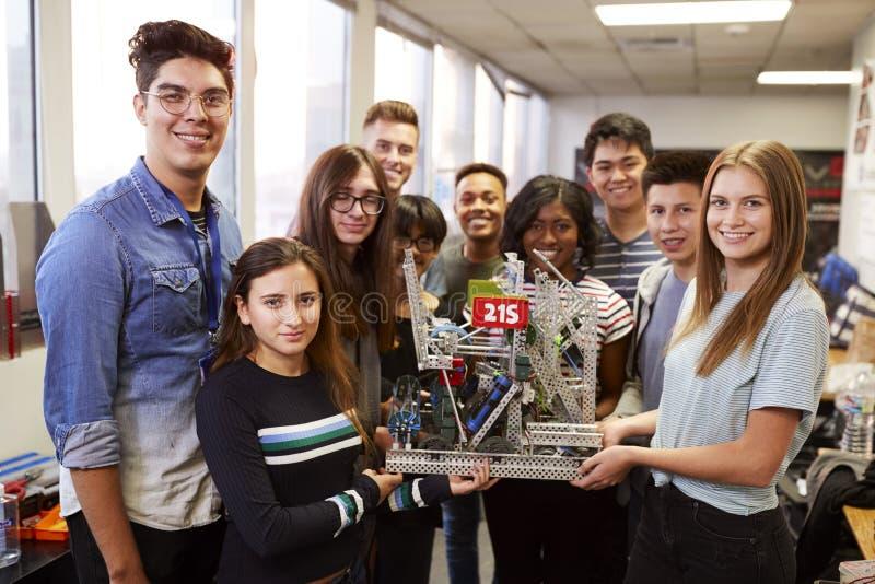 Stående av universitetsstudenter med lärareHolding Machine In vetenskap eller robotteknikgrupp royaltyfri fotografi