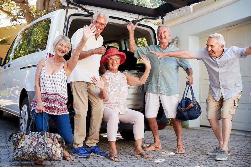 Stående av upphetsade höga vänner som omkring laddar bagage in i stammen av bilen för att lämna för semester royaltyfria bilder