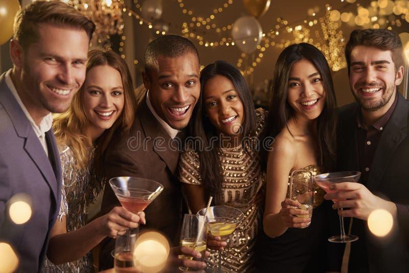 Stående av vänner med drinkar som tycker om cocktailpartyet