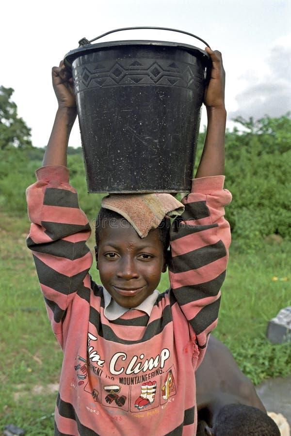 Stående av vatten som bär den ghananska pojken, Ghana arkivbild
