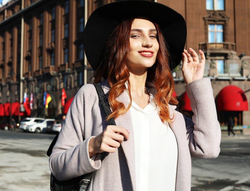 Stående av yong den härliga lyckliga le kvinnan som bär den stilfulla hatten, lag Modellera att gå i gata av den europeiska stade arkivbilder