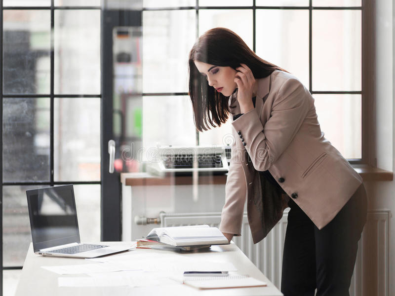Stående benägenhet för affärskvinna på skrivbordet i regeringsställning royaltyfri foto