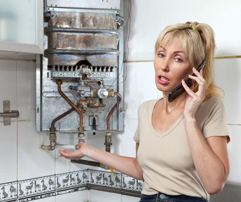 Stående den unga kvinnan som hemmafrun kallar i ett seminarium på reparation av gasvattenvärmeapparater arkivfoton