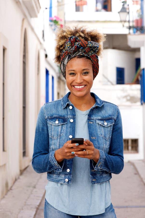 Stående det fria för härlig ung afrikansk kvinna med den smarta telefonen arkivfoto