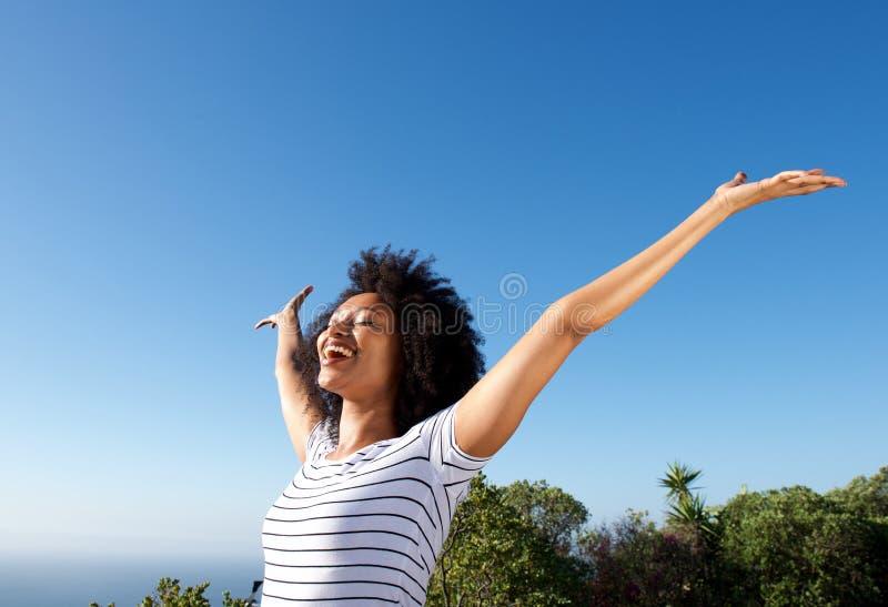 Stående det fria för ung afrikansk kvinna med lyftta armar och att skratta arkivfoton
